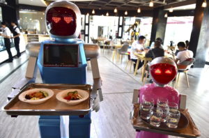 Robot couple Xiaolan (L) and Xiaotao carry trays of food at a restaurant in Jinhua, Zhejiang province, China, May 18, 2015. The restaurant, which opened on Monday has two robots delivering food for customers. The robots were designed as a couple, Xiaolan and Xiaotao, according to local media. REUTERS/Stringer CHINA OUT. NO COMMERCIAL OR EDITORIAL SALES IN CHINA - RTX1DGH4